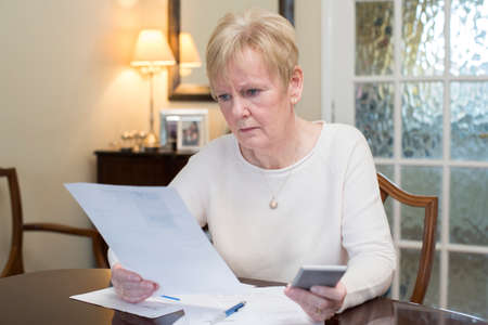 Concerned Senior Woman Reviewing Domestic Finances Stockfoto