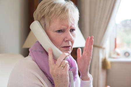 Senior Woman Receiving Unwanted Telephone Call At Home Foto de archivo