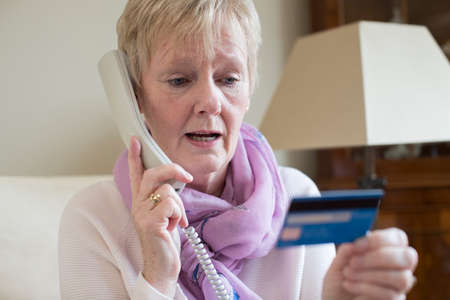 Senior Woman Giving Credit Card Details On The Phone