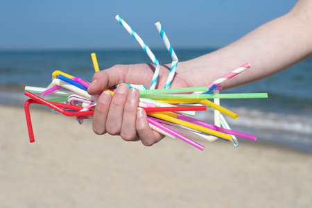 Close Up Of Hand Holding Plastic Straws Polluting Beach Banque d'images