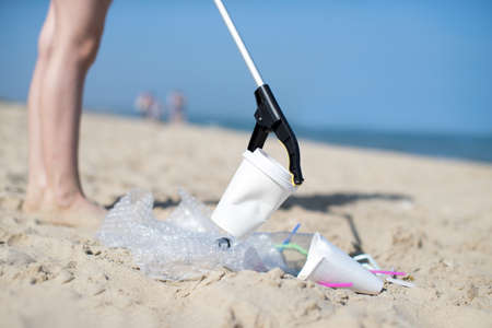 Close Up Of Person Collecting Plastic Waste From Polluted Beach Using Litter Picker