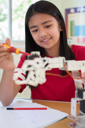 Female Pupil In Science Lesson Studying Robotics
