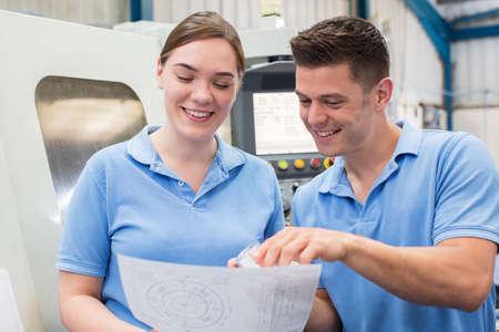 Engineer Instructing Female Apprentice On Use Of CNC Machine