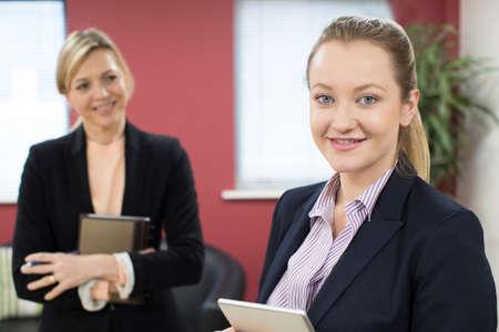 Portrait Of Young Businesswoman With Female Mentor In Office