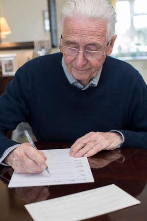 Älterer Mann, der letzten Willen und Testament zu Hause unterschreibt