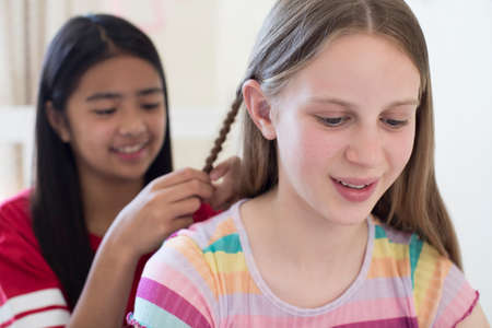 Two Girls In Bedroom Braiding Each Others Hair