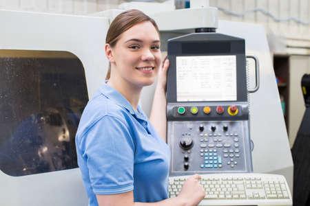 Portrait Of Female Apprentice Engineer Operating CNC Machine In Factory Stock fotó