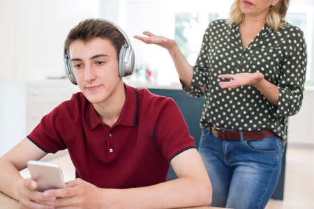 Teenage Boy Wearing Headphones And Using Mobile Phone Being Nagged By Mother At Home Stock Photo - 106145181