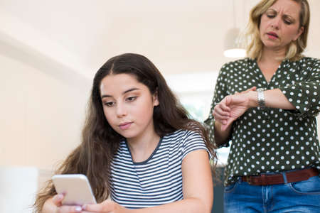 Mother Arguing With Teenage Daughter Over Use Of Mobile Phone 免版税图像