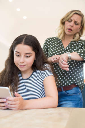 Mother Arguing With Teenage Daughter Over Use Of Mobile Phone Stock Photo