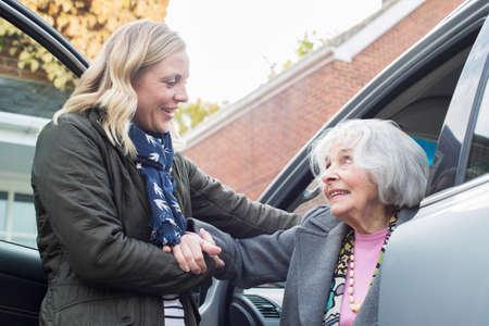 Weibliche Nachbarin, die ältere Frau im Auto mitnimmt