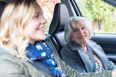 Female Neighbor Giving Senior Woman A Lift In Car Archivio Fotografico