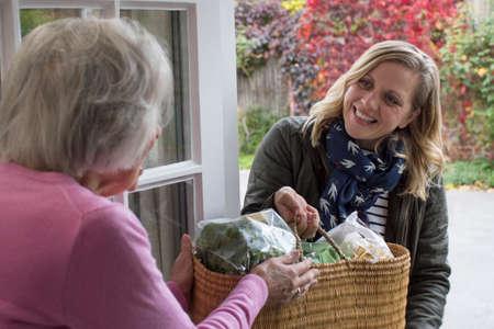 Voisine aidant une femme âgée à faire du shopping Banque d'images
