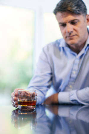 Unhappy Mature Man With Alchol Problem Holding Glass Of Whiskey At Home