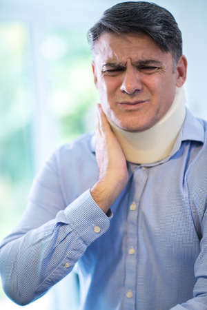 Mature Man Wearing Neck Brace Winces With Pain Stock fotó