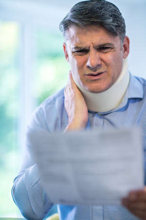Mature Man Reading Letter After Receiving Neck Injury