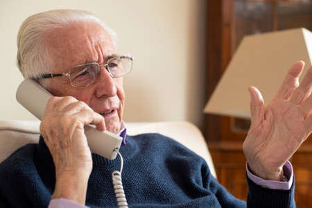 Senior Man Receiving Unwanted Telephone Call At Home