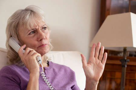 Senior Woman Receiving Unwanted Telephone Call At Home Stock Photo