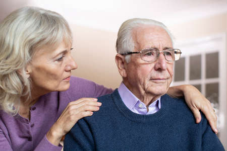 Confused Senior Man Suffering With Depression And Dementia Being Comforted By Wife