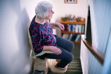 Senior Woman Sitting On Stair Lift At Home To Help Mobility Фото со стока