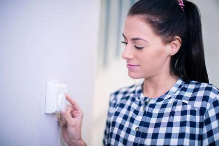 Kobieta w domu regulująca sterowanie termostatem centralnego ogrzewania