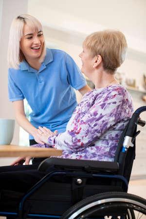 Vrouwelijke zorgassistent in gesprek met senior vrouw die thuis in een rolstoel zit
