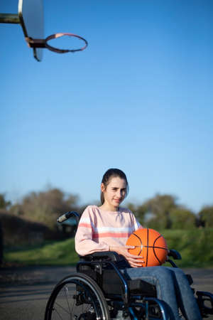Portrait Of Teenage Girl In Wheelchair Playing Basketball Banco de Imagens