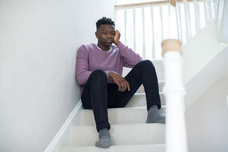 Fed Up Teenage Boy Sitting On Stairs At Home