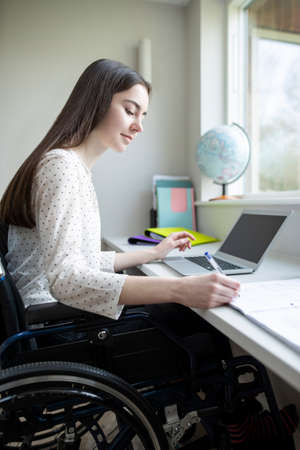 Teenage Girl In Wheelchair Studying At Home On Laptop Stock Photo