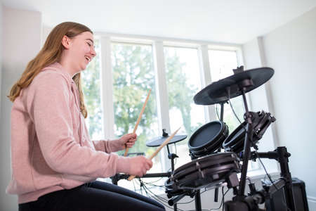 Teenage Girl Having Fun Playing Electronic Drum Kit At Home Reklamní fotografie