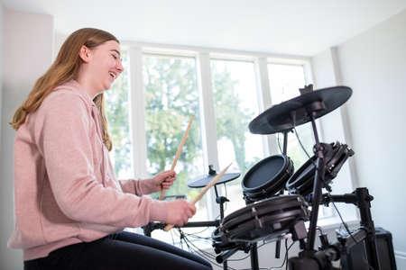 Teenage Girl Having Fun Playing Electronic Drum Kit At Home 스톡 콘텐츠