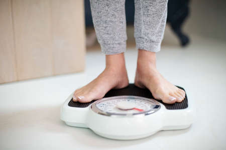 Close Up Of Woman Standing On Bathroom Scales At Home