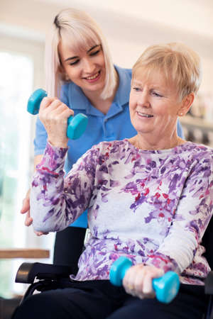Female Physiotherapist Helping Senior Woman In Wheelchair To Lift Hand Weights Stock Photo