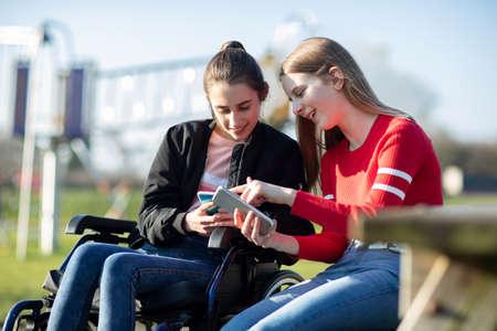 Teenager-Mädchen im Rollstuhl auf der Suche nach Handy mit Freund im Park Standard-Bild