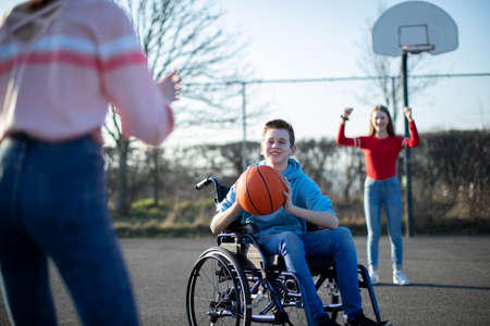 Teenage Boy In Wheelchair Playing Basketball With Friends Archivio Fotografico