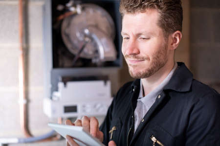 Male Heating Engineer Servicing Central Heating Boiler Using Digital Tablet