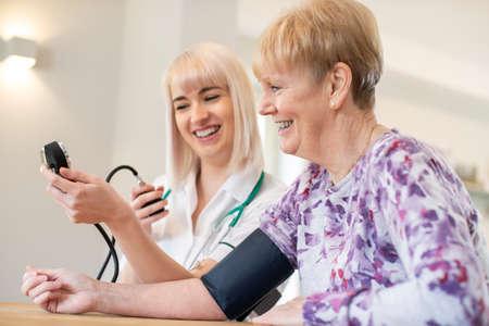 Nurse Measuring Blood Pressure Of Senior Woman At Home