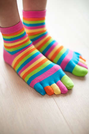 Close Up Of Woman Wearing Brightly Colored Socks On Feet Standing On Wooden Floor