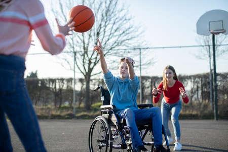 Adolescente en silla de ruedas jugando baloncesto con amigos