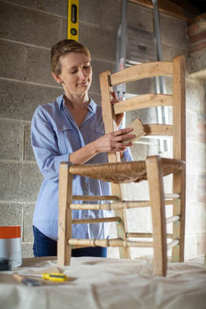 Mature Woman Upcycling Chair In Workshop At Home