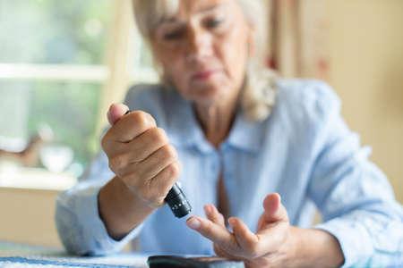 Senior Woman Testing Blood Sugar Level At Home