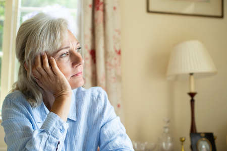 Senior Woman Suffering With Depression Looking Out Of Window At Home