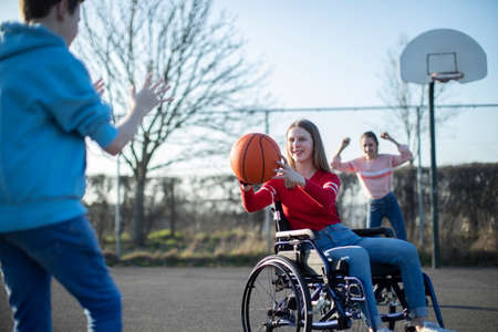 Teenage Girl In Wheelchair Playing Basketball With Friends