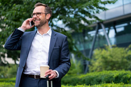 Mature Businessman Taking Phone Call On Mobile Phone Standing Outside Office Building 版權商用圖片