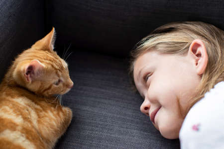 Girl Lying On Sofa At Home Looking Lovingly At Pet Cat