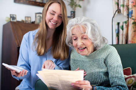 Woman Helping Senior Neighbor With Bills And Paperwork