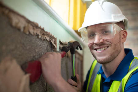Portrait Of Construction Worker With Chisel Removing Plaster From Wall In Renovated House