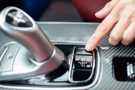 Close Up Of Driver Pressing Switch To Engage Electric Motor In Hybrid Car