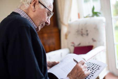 Senior Man Doing Crossword Puzzle At Home