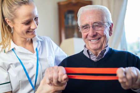 Female Physiotherapist Helping Senior Man To Use Resistance Band At Home